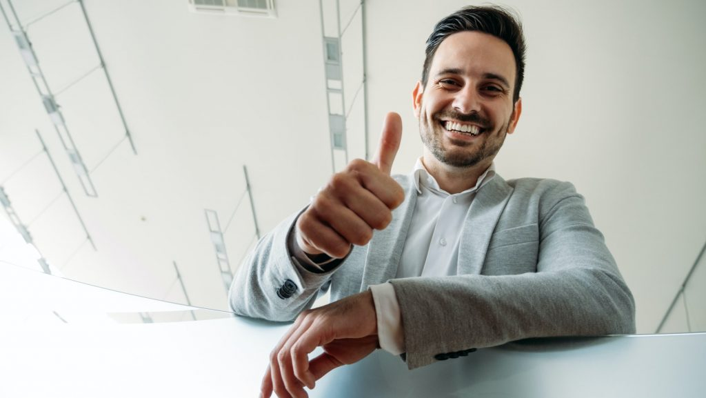 Happy business man shows thumb up sign gesture